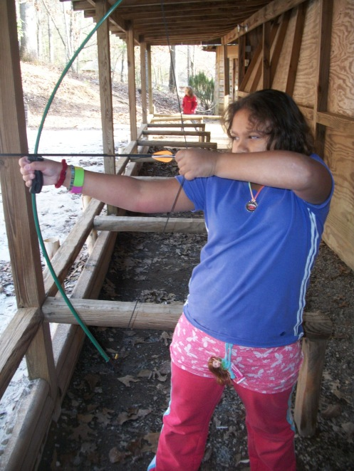 My daughter  at the archery range. See the concentration in those eyes!